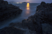 Scenic view of sea and rocks at night