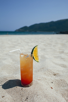 Glass of refreshment on sand at beach during sunny day