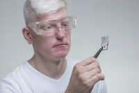 Albino man wearing protective eyewear while examining chip against gray background