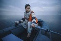 Teenage girl wearing life jacket while rafting in lake