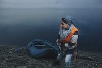 Teenage girl pulling inflatable raft to lakeshore