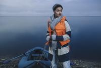 Teenage girl with inflatable raft standing on lake