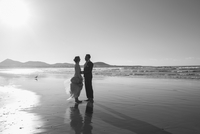 Full length side view of loving bride and groom standing at beach