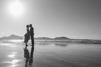 Full length side view of bride and groom kissing at beach against clear sky