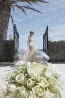 Portrait of happy bride standing at entrance with rose bouquet in background