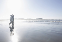 Full length of loving bride and groom standing at beach