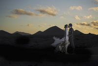 Full length side view of bridge and groom kissing on volcanic landscape during sunset