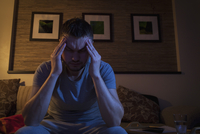 Man suffering from headache while sitting on sofa at home