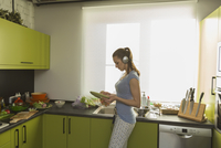 Side view of woman listening music while cleaning plate in kitchen