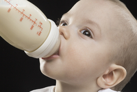 Close-up of boy drinking milk from bottle against black background