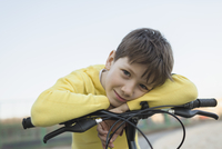 Portrait of smiling boy leaning on bicycle against clear sky