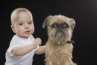 Portrait of boy with dog against black background