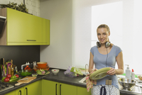 Portrait of happy woman with headphones while cleaning plate in kitchen