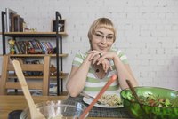 Portrait of smiling woman having spaghetti while sitting at table