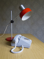 Rotary phone and electric lamp on table at home