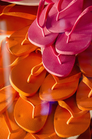 Full frame shot of pink and orange flip-flops seen through glass at store