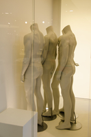 Mannequins against wall seen through glass at store