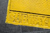 High angle view of yellow subway text on metal
