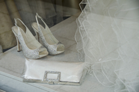 High angle view of stilettos and purse with dress for display at bridal shop