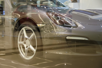 Cropped image of car seen through glass at showroom