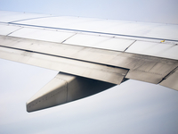 Cropped image of airplane wing flying in sky