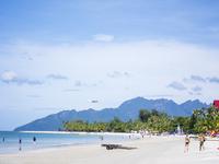 People enjoying at beach in Pulau Langkawi against sky