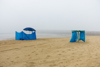 Blue tent and parasol by garbage bags at beach against sky during foggy weather