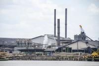 Industrial buildings at riverbank against sky