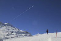 Rear view of person hiking on snow covered mountain against blue sky 11016033093| 写真素材・ストックフォト・画像・イラスト素材|アマナイメージズ