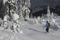Man walking on snow covered field against mountains 11016033100| 写真素材・ストックフォト・画像・イラスト素材|アマナイメージズ