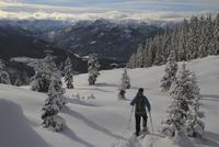 Rear view of man hiking on snow covered mountain 11016033107| 写真素材・ストックフォト・画像・イラスト素材|アマナイメージズ