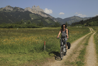 Woman riding bicycle on road by grassy field against mountains 11016033113| 写真素材・ストックフォト・画像・イラスト素材|アマナイメージズ