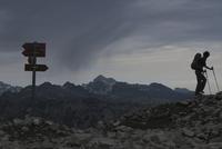 Woman hiking on rocks at mountain against cloudy sky 11016033129| 写真素材・ストックフォト・画像・イラスト素材|アマナイメージズ