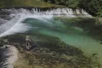 Rear view of man fishing at river 11016033130| 写真素材・ストックフォト・画像・イラスト素材|アマナイメージズ