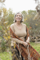 Smiling mature woman looking away while standing at park during autumn 11016033135| 写真素材・ストックフォト・画像・イラスト素材|アマナイメージズ