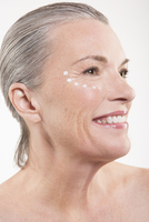 Close-up of happy mature woman with dots of moisturizing cream on face against white background 11016033138| 写真素材・ストックフォト・画像・イラスト素材|アマナイメージズ