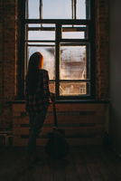 Full length rear view of woman with guitar standing by window at home 11016033150| 写真素材・ストックフォト・画像・イラスト素材|アマナイメージズ