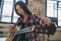 Low angle view of young woman playing guitar at home 11016033151| 写真素材・ストックフォト・画像・イラスト素材|アマナイメージズ
