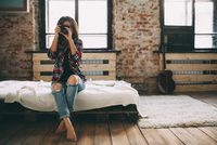 Full length of woman photographing through SLR camera in bedroom at home 11016033152| 写真素材・ストックフォト・画像・イラスト素材|アマナイメージズ