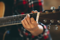 Cropped image of young woman playing guitar at home 11016033153| 写真素材・ストックフォト・画像・イラスト素材|アマナイメージズ