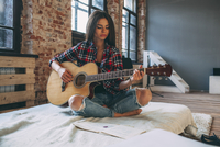 Young woman playing guitar while sitting on bed at home 11016033155| 写真素材・ストックフォト・画像・イラスト素材|アマナイメージズ
