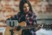 Smart phone in monopod with woman playing guitar in background at home 11016033157| 写真素材・ストックフォト・画像・イラスト素材|アマナイメージズ