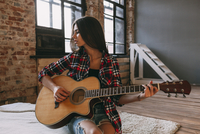 Young woman playing guitar at home 11016033160| 写真素材・ストックフォト・画像・イラスト素材|アマナイメージズ