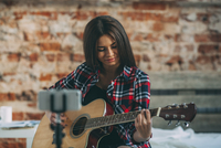 Smart phone in monopod with woman playing guitar at home 11016033162| 写真素材・ストックフォト・画像・イラスト素材|アマナイメージズ