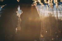 Young couple touching foreheads while standing on field during winter 11016033165| 写真素材・ストックフォト・画像・イラスト素材|アマナイメージズ