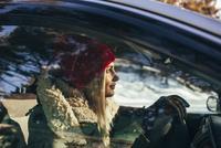 Woman in warm clothing driving car 11016033176| 写真素材・ストックフォト・画像・イラスト素材|アマナイメージズ