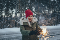 Happy woman holding sparklers while standing on field during winter 11016033177| 写真素材・ストックフォト・画像・イラスト素材|アマナイメージズ