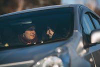 Happy young couple romancing in car