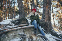 Full length of young woman sitting in snow covered forest 11016033181| 写真素材・ストックフォト・画像・イラスト素材|アマナイメージズ