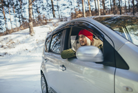Happy young woman in car during winter